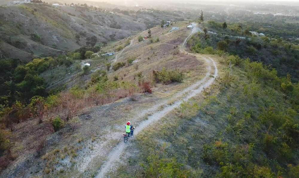 Ariel photo of man riding motorbike on dirt path