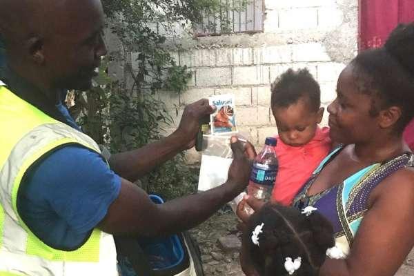 MotoMeds Driver giving medication to mother holding child