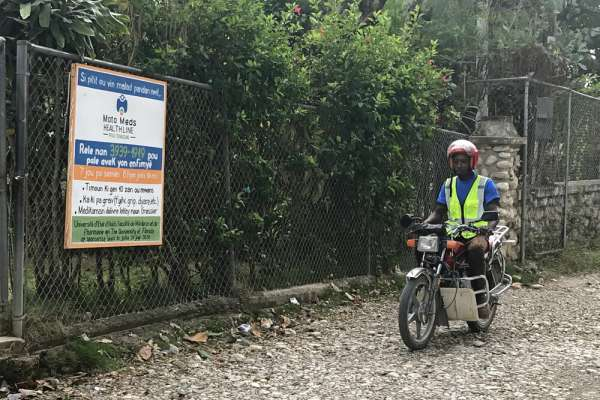Man on motorbike delivering medicine